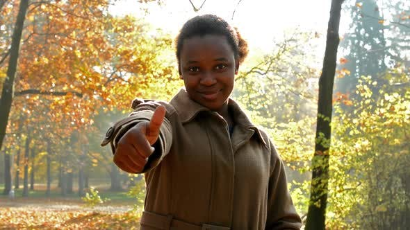 Thumbnail for Young Beautiful Happy African Girl Stare Into Camera, Shows the Thumbs-up and Stands in the Woods