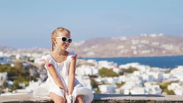 Thumbnail for Portrait of Adorable Little Girl Background Mykonos Town in Europe
