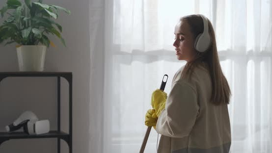 Singing Housekeeper Is Dancing with Mop in Living Room Cleanup and Housekeeping Medium Portrait
