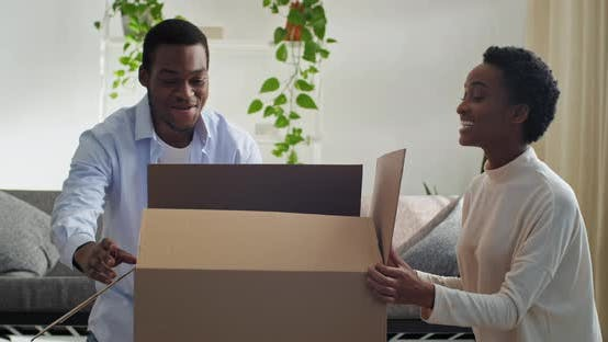 Thumbnail for Afro American Couple Wife and Husband Opens Cardboard Box Looks Wondering Child Daughter Little Girl