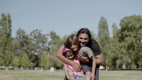 Long Shot of Disabled Father Hugging Daughter and Son in Park