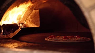 Pizza Being Cooked in a Wood Fired Stone Oven