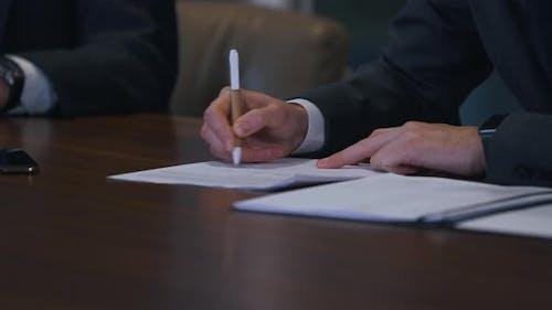 Businessman Puts Signature on Document Closeup