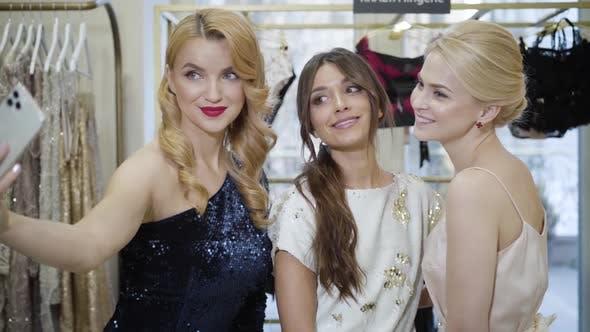 Thumbnail for Porträt von drei schönen kaukasischen Modemodellen in eleganten Kleidern nehmen Selfie. Kamera
