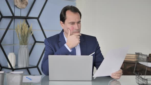 Thumbnail for Businessman Reading Documents in Office