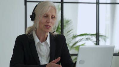 Elderly Lady in a Headset Talks on a Video Conference Conducts a Video Conference Using a Laptop in