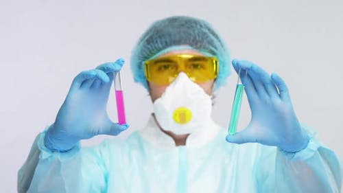 Laborant in Biohazard Suit Showing Two Sample of Antivirus To Covid-19