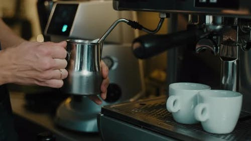 Barista steaming milk for  specialty coffee latte art