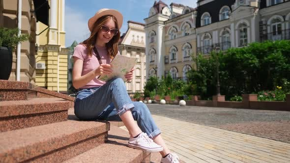 Thumbnail for Beautiful Young Woman Tourist Pleasant with City Map Sitting on Stairs in the City Center