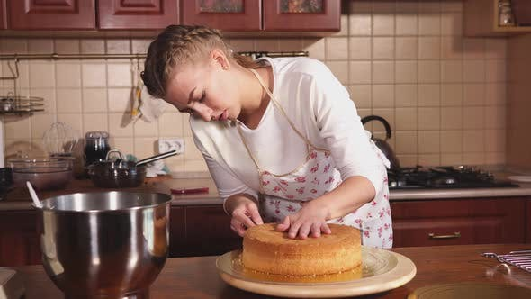 Thumbnail for a Woman Who Works As a Chef Cuts Freshly Baked Cakes with a Knife