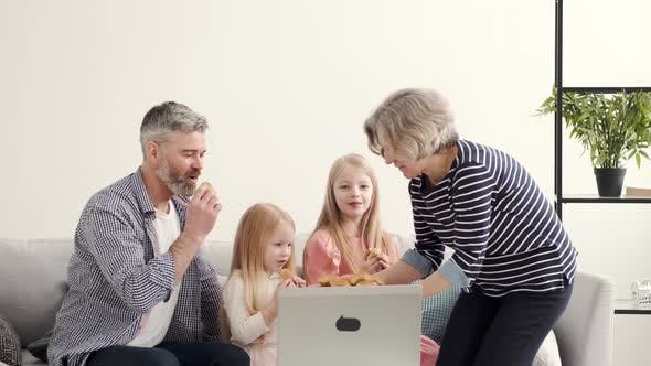 Grandarents with Granddaughters Using Laptop in the Living Room