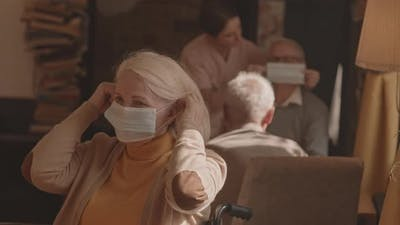 Senior Woman Putting on Protective Face Mask