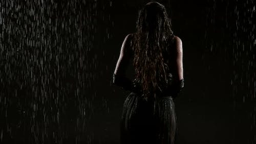 Sexy Young Woman with Stunning Figure is Standing Under Rain at Night Rear View in Her Silhouette