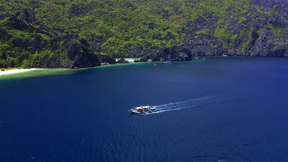 Thumbnail for Aerial Drone View of White Traditional Filipino Boat Floating on Top of Clear Blue Water Surface