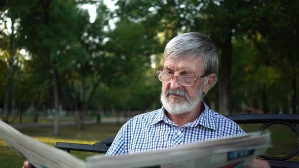 Thumbnail for Senior in Plaid Shirt Sits on a Bench in the Park and Reads a Newspaper