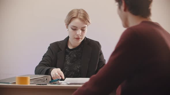 Thumbnail for Man  Bringing a Document To a Woman She Is Putting a Signature and Stamp