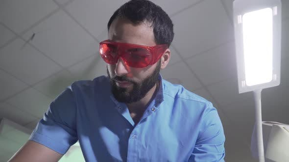 Thumbnail for Serious Middle Eastern Man in Blue Uniform and Protective Eyeglasses Preparing for Patient Visit