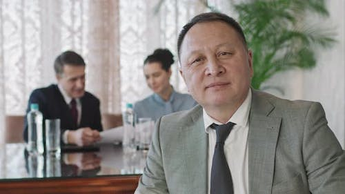 Portrait Of Smiling Asian Business Man At Conference Table