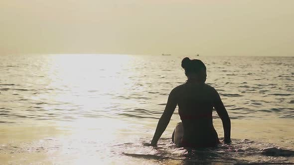 Silhouette of Woman Resting in Rolling Sea Waves Slow Motion