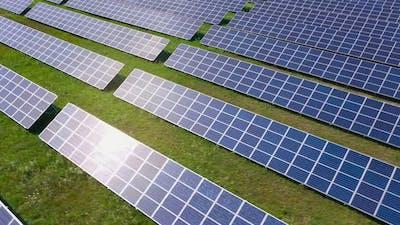 Flight Over a Field of Solar Panels in Sunny Summer Day