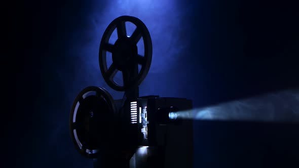 Thumbnail for Projection Rays. Film Projector Turns Film in Smoky Dark Studio