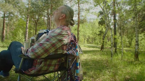 Peaceful Middle Aged Male Camper Relaxing in Summer Nature at Campsite