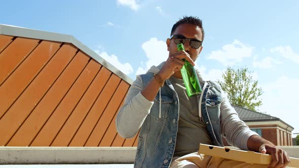 Cover Image for Indian Man Eating Pizza and Drinking Beer Outdoors