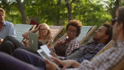 Five Interracial Friends Lying on Recliners in Park with Laptop Notebooks Tablets Speaking Smling