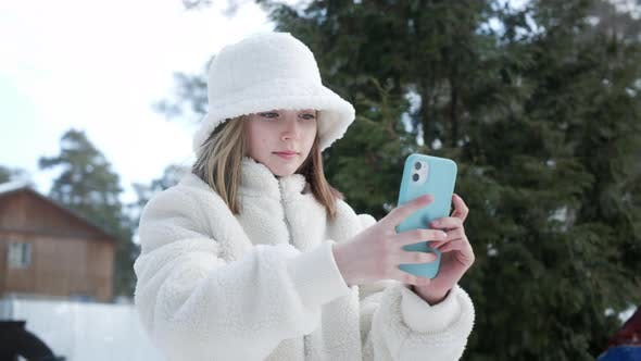 Focused Young Girl in Stylish Outfit Using Smartphone Outdoors at Wintertime