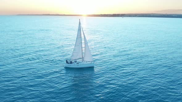 Thumbnail for Aerial View. The Yacht Sails on the Sea at Sunset. Drone Flies Around the Yacht with Sails.