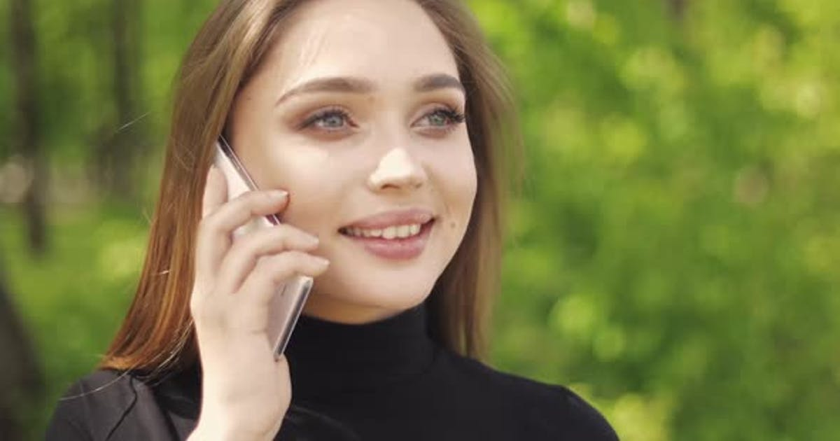 Portrait of Beautiful Female Talking Phone and Laughing While Looking Away