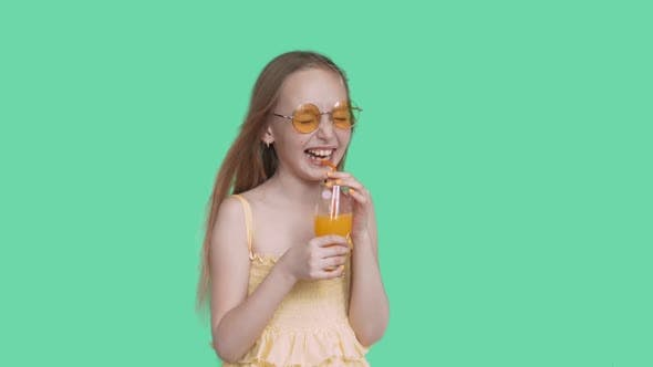 Laughing Happy Teen Girl in Glasses and Dress Drinking Juice on Green Screen