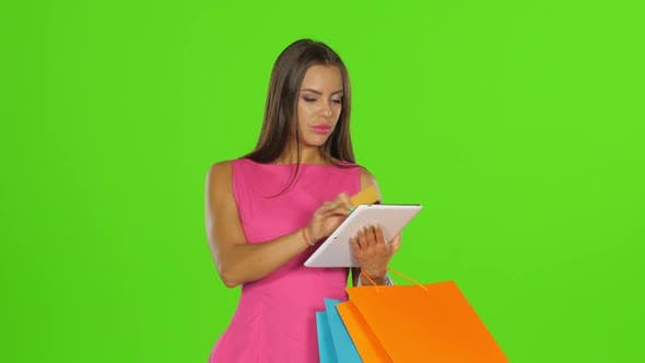 Thumbnail for Woman Does Shopping with Credit Card and Tablet. Green Screen. Close Up