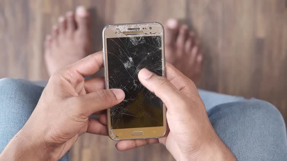 Top View of Man Hand Holding Broken Smart Phone White Sited