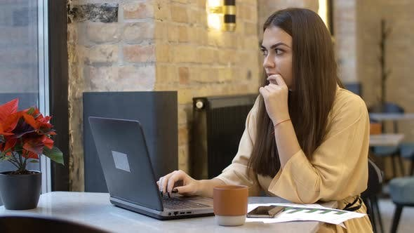 Thumbnail for Absorbed Beautiful Young Woman Typing on Laptop Keyboard and Thinking