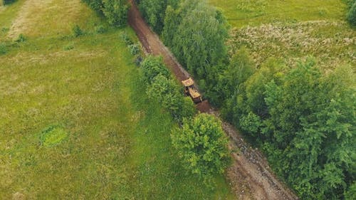 Aerial View A Bulldozer Leveling a Road Destroyed By Floods in a Mountainous Area. Heavy Machinery