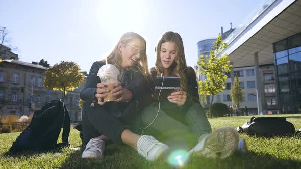 Thumbnail for Happy Teenage Friends Using Tablet Computer Computer at Park in Centre of the Town