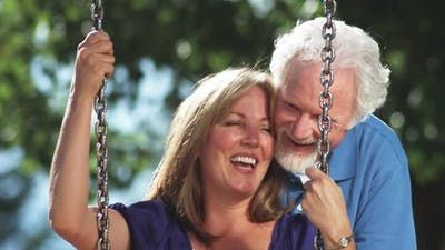 Happy older couple on a park swing.