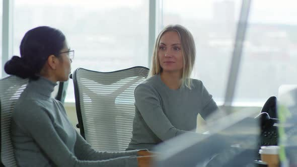 Women Sitting at Desk in Office and Talking