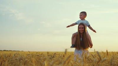 Little Boy on Shoulders of Mom Walking in Field