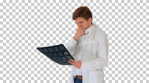 Frustrated male doctor examining computed, Alpha Channel