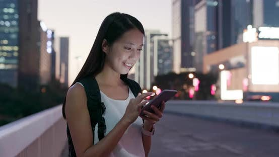 Cover Image for Woman work on mobile phone in city at evening time