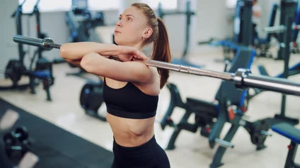 Thumbnail for Young Woman with a Tail Performs Squats with a Barbell in the Gym