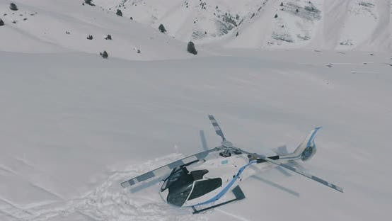 Thumbnail for The aerial flies over a parked helicopter standing in the snow in the winter mountains