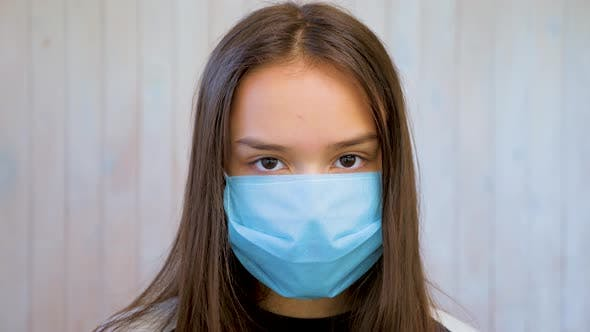 Thumbnail for Portrait of Beautiful Brunette Teen Girl in Medical Protective Mask Over Light Gray Wall Background