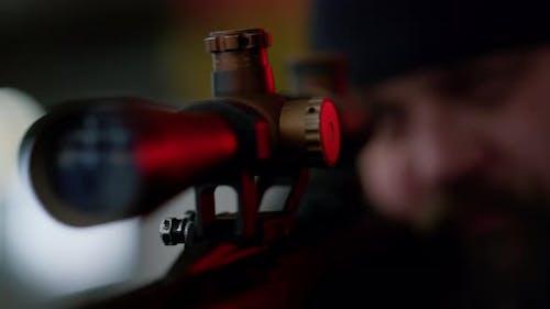 Gewalttätiger Mann, der auf modernes Gewehr abzielt