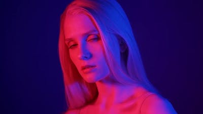 Portrait of a Stylish Blonde Model in Colored Lighting