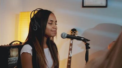 Black Girl in Headphone Singing Into Microphone at the Rehearsal in Home Studio