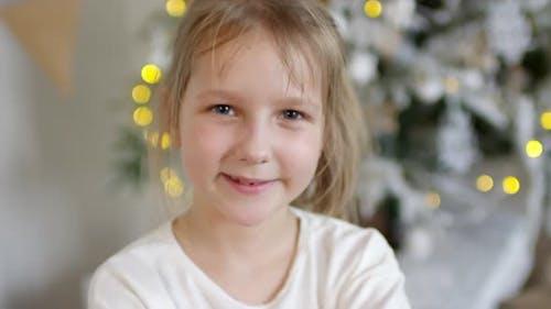 Joyous Little Girl Posing for Camera near Christmas Tree