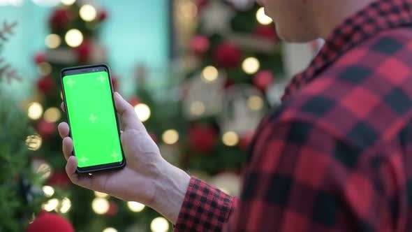 Cover Image for Rear View Of Young Hipster Man Using Phone Against Christmas Trees Outdoors